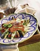 Veal steak with asparagus stuffing on asparagus salad