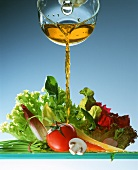 Kräuteröl wird auf gemischten Salat gegossen