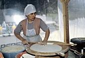 Türkische Frau beim Ausrollen von Teig für Fladenbrote