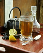 Punch in tall glass, teapot, lemon and carafe of rum