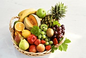 Various fruits and galia melon in wicker basket