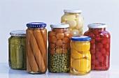 Six preserving jars with vegetables, fruit, sausages