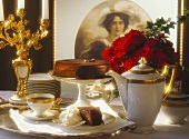Sacher torte on festive coffee table, decor: picture, roses
