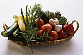 Assorted fresh vegetables and herbs on wicker tray