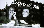 Man and woman through the window of an espresso bar