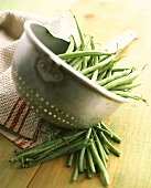 Green beans (French beans) in strainer & beside it on table
