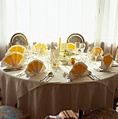 Round table laid for wedding with white & yellow napkins