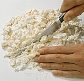 Making sweet pastry (chopping mixed ingredients with knife)