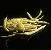 Yellow beans on black shiny background