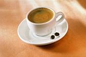 Eine Tasse Kaffee und zwei Kaffeebohnen auf dem Unterteller