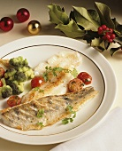Fried pike-perch with vegetables on plate; holly