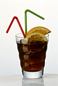 Glass of cola with ice cubes, lemon slices & 2 straws