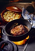 Roast wild boar in roasting dish on cooker, potato casserole