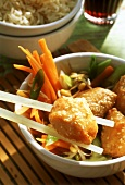 Chicken pieces with sesame(one on chopstick), vegetables