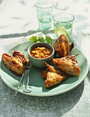 Glazed chicken wing with mango and chili sauce on plate