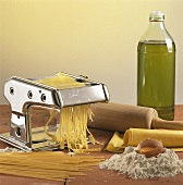 Pasta machine with pasta dough, pasta, ingredients, rolling pin