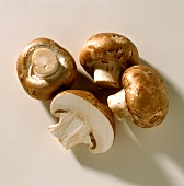 Three whole and one half brown mushrooms