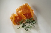 A slice of smoked salmon and sprig of dill