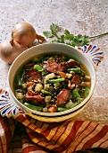 Lentil soup with sausage, beans & potatoes in soup bowl