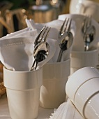 Cutlery and napkins in ceramic mugs (table decoration)