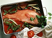Red perch on tomato sauce with vegetables in cooking dish