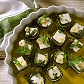 Sheep's cheese & courgette snacks in a dish with olive oil