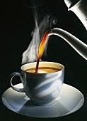 Kaffee wird in Tasse gegossen, schwarzer Hintergrund