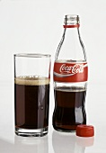 Small bottle of Coca Cola, opened & a glass of Cola