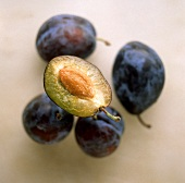 Four plums & half a plum with stone