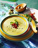 Herb cream soup with salami strips in soup plate