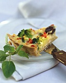 A piece of broccoli quiche with vegetables & olives