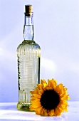 A bottle of sunflower oil and sunflowers