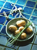 Potatoes and a bunch of chives in weighing scales