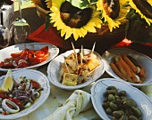 Spanish tapas on platters on garden table with sunflowers