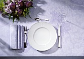 Place setting (plate, cutlery, wineglass) on violet tablecloth