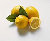 Drei Zitronen mit zwei Blättern und eine Zitronenhälfte