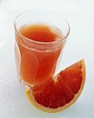 Ein Glas Grapefruitsaft und ein rosa Grapefruitschnitz