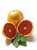 Halbierte rosa Grapefruit mit zwei Blättern vor ganzer Frucht
