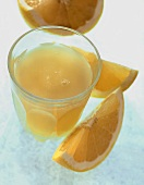 Glas Grapefruitsaft und gelbe Grapefruitschnitze