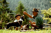 Man, boy and dog with snack in a mountain pasture