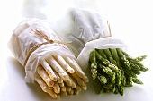 Bundles of green and white asparagus wrapped in paper