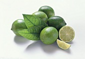 Five limes with leaves, lime half and wedge