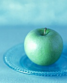 A Granny Smith Apple on a Glass Plate