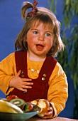 Kleines Mädchen mit angebissener Birne vor Obstschale