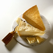 Pieces of parmesan with cheese knife on round marble slab