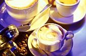 Cup of cappuccino, latte macchiato & espresso on table