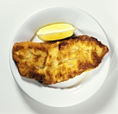 Wiener Schnitzel and a slice of lemon on plate