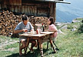 Couple Having a Picnic Outdoors with a View of the Alps