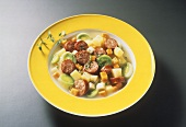 Vegetable stew with sausage slices on yellow plate
