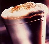 Aufgeschäumte Milch (für Cappuccino) im Metallbecher